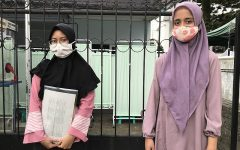 photo of two vaccine volunteers hoping to achieve immunity. both have face masks and head coverings on.