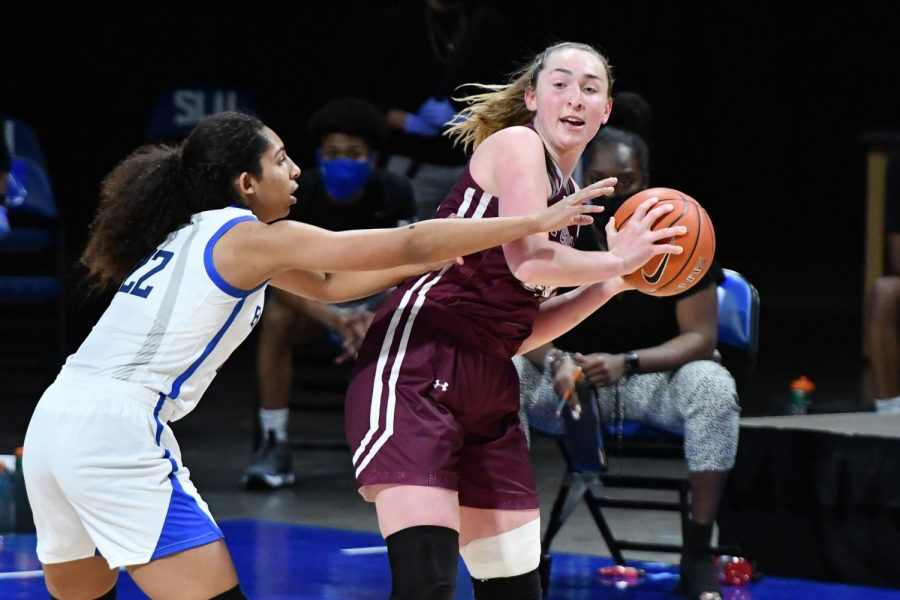 kaitlyn downey in a maroon uniform holding a basketball while a saint louis player, to the left of her in a white uniform, reaches over and tries to take it
