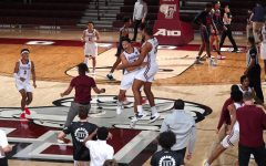 fordham basketball players jump and hug each other on the court after a win over dayton