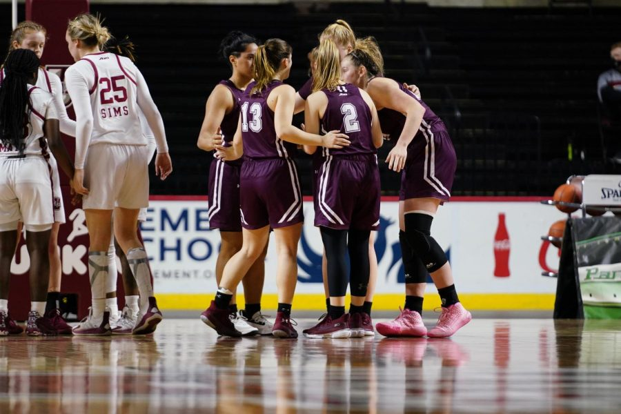 fordham basketball players in a huddle on a basketball court during a game against umass