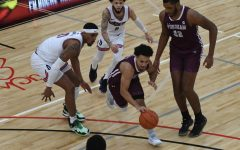 basketball player josh navarro dribbles a ball down a basketball court surrounded by one fordham player and two duquesne players