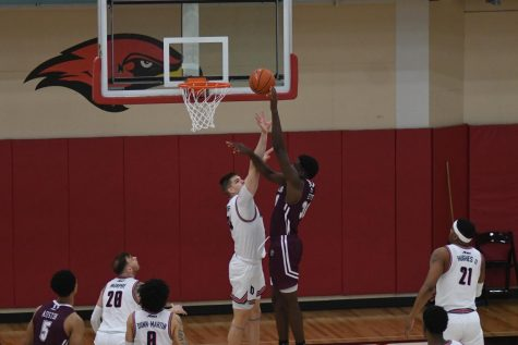 fordham player attempting to shoot over a duquesne player