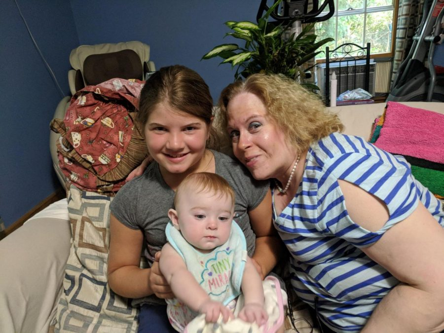 Laura Greeney poses with her great-nieces on a couch