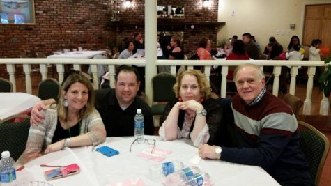 Laura Greeney sits at a restaurant table with her family members