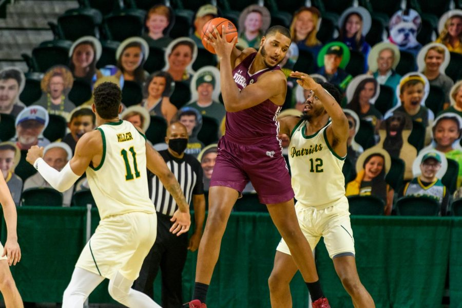 photo of a fordham player on the basketball court with a george mason player on either side of him