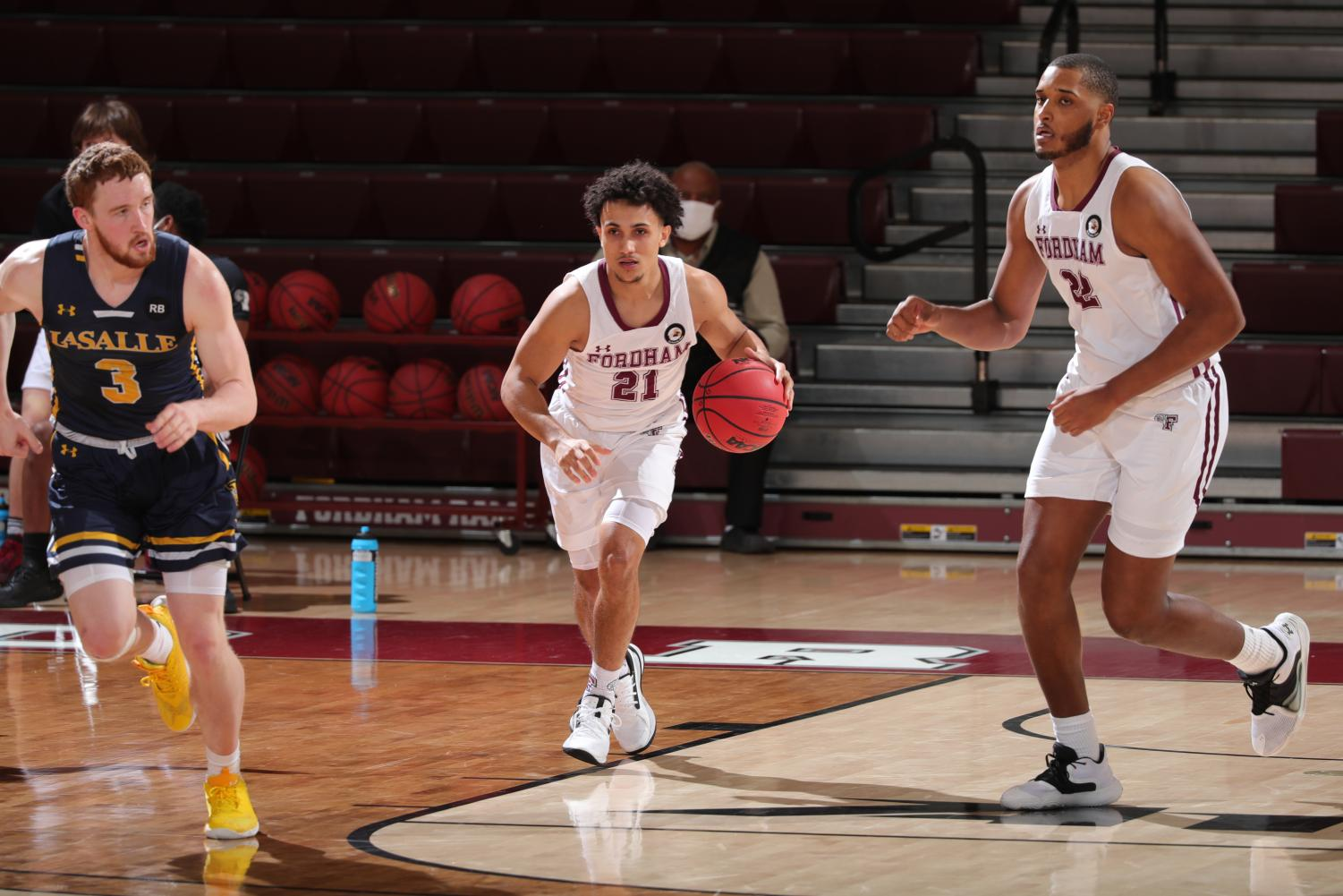 josh navarro brings a basketball down the court against la salle. a la salle player is to his left and a fordham player is to his right