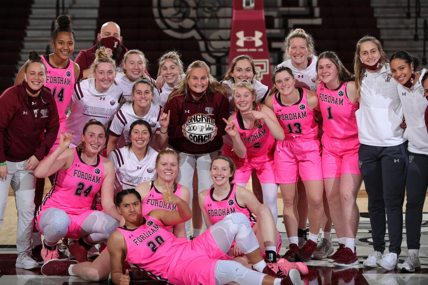 group photo of fordham women's basketball team and their coach smiling after defeating URI