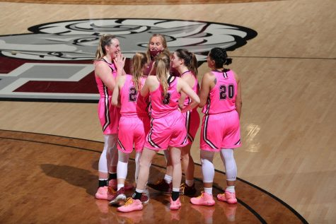 fordham basketball players in pink uniforms in a huddle after their game against saint joseph's