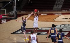 in a game against la salle, ty perry shoots a basketball on the court. he is wearing a white uniform, and three la salle players in navy uniforms are around him. one other fordham player in white is in the foreground