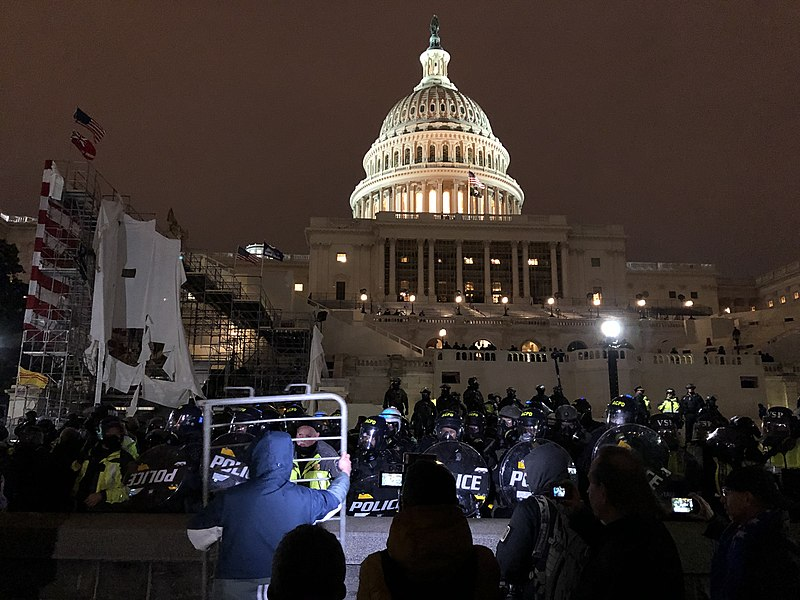 protestors gather at night outside the US Capitol building as police barricade the front steps