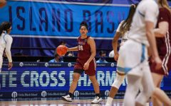 in an article about women's basketball postponing games, player kendell heremaia on the court holding a basketball