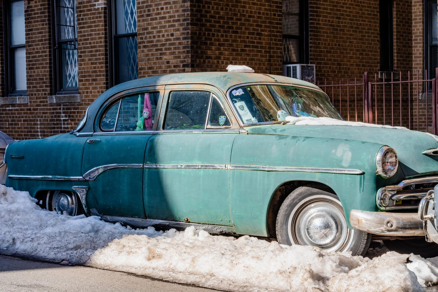 a turquoise vintage car in little odessa in a snow mound
