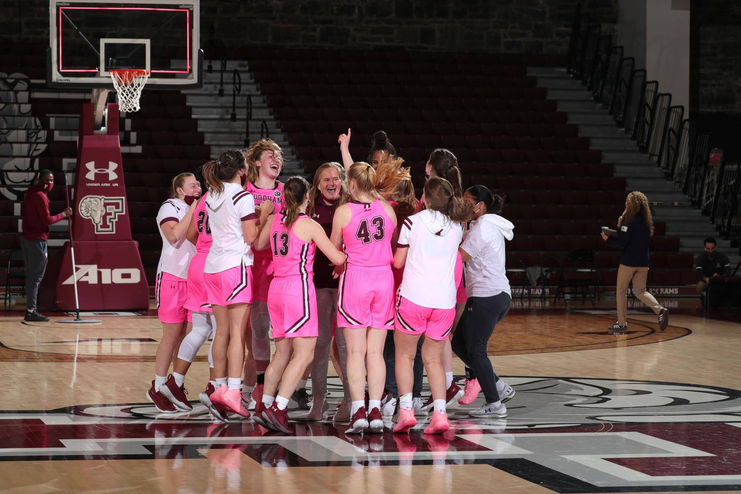 fordham women's basketball team jumping up and down in a huddle around their coach in the middle of a basketball court after defeating URI