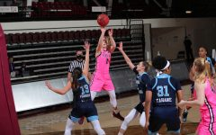 anna dewolfe jumping to make a basket in a game against URI. she is surrounded by three URI players in blue uniforms and one fordham player in a pink uniform