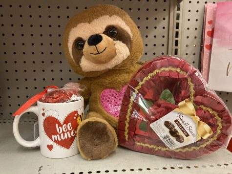 stuffed sloth, mug with a heart on it and box of chocolate