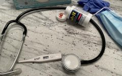 for an article about covid effects on the brain, photo of a stethoscope, a bottle of advil, gloves, tissues and a mask on a table