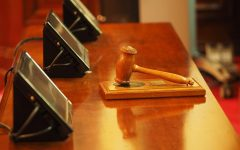 a gavel rests in front of screens on a courtroom desk