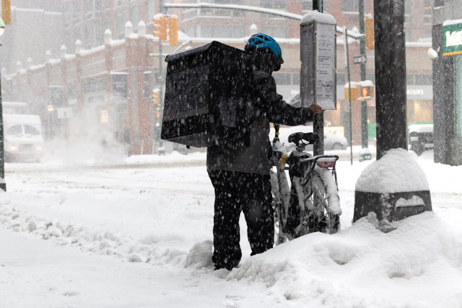 a delivery worker brushes snow of their bike