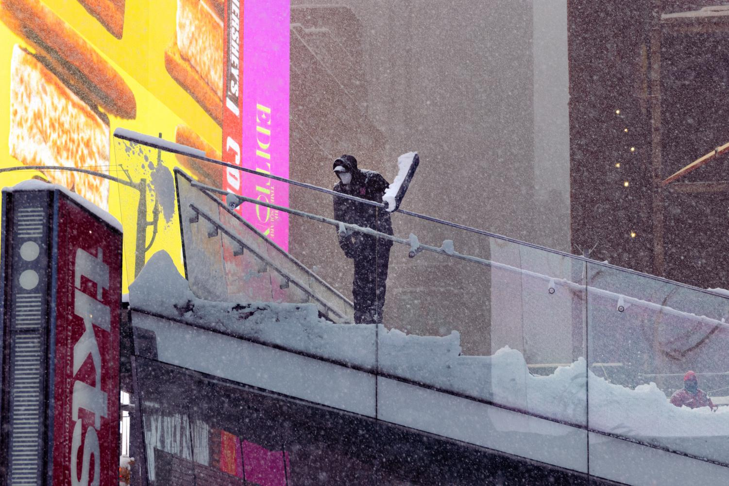 someone shoveling off the top of the stairs at Times Square