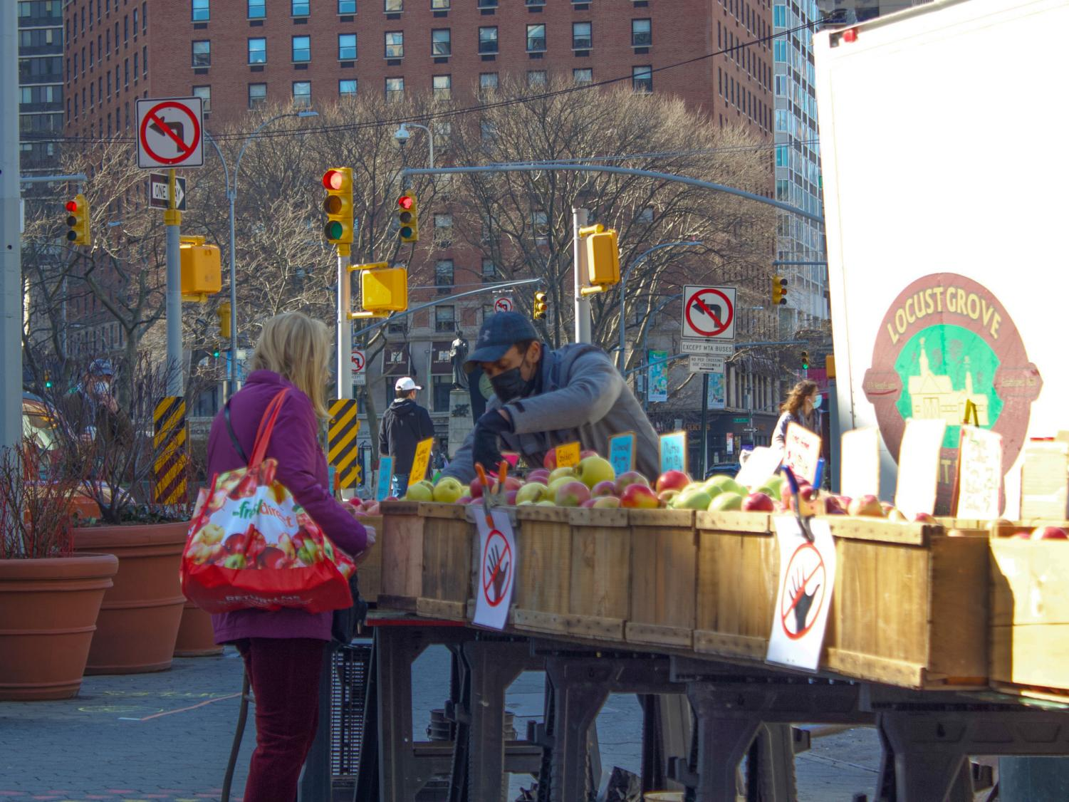 person looking at fruit in boxes at a spring farmer's market