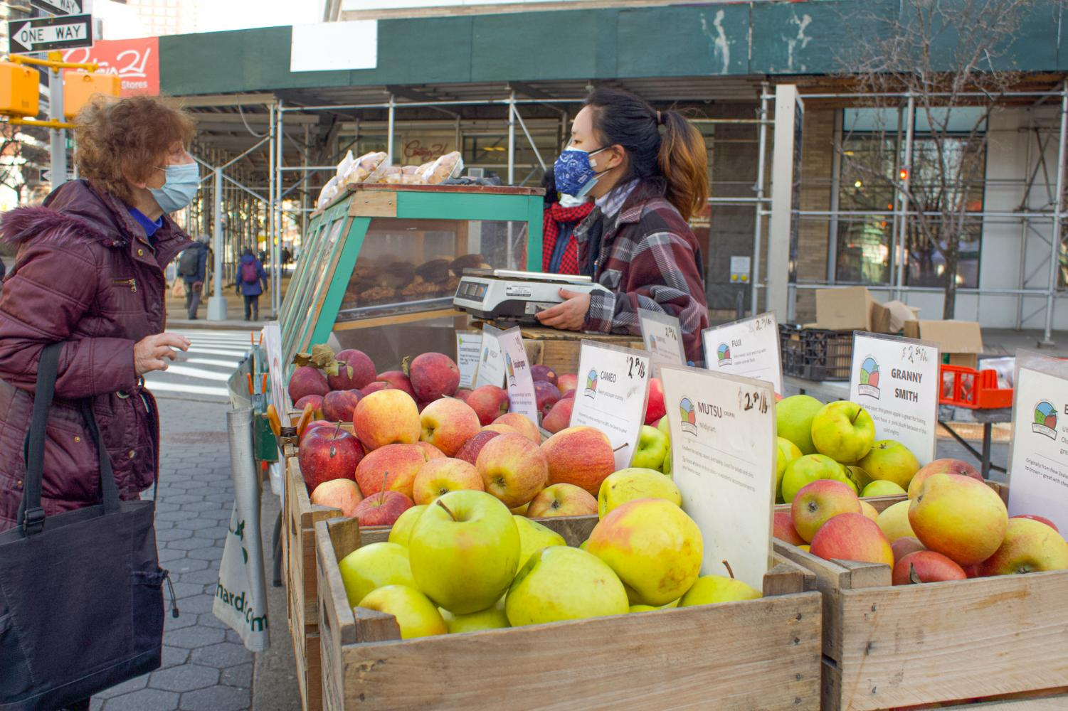woman looking at apples in boxes at an outdoor spring farmer's market