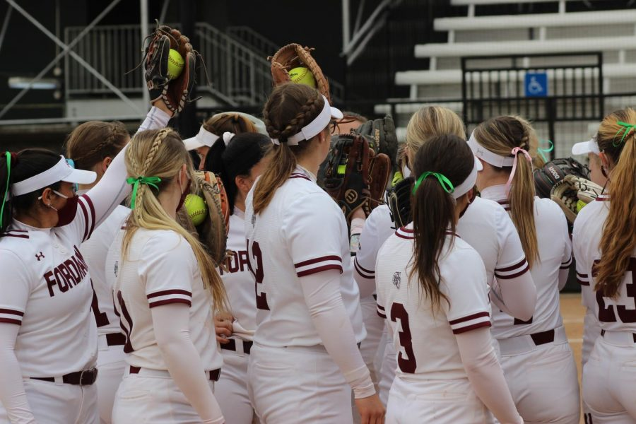 the Fordham softball team huddles up during a game