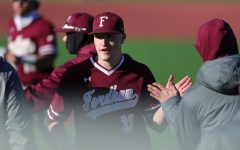 Fordham baseball player Matt Mikulski high fives a teammate