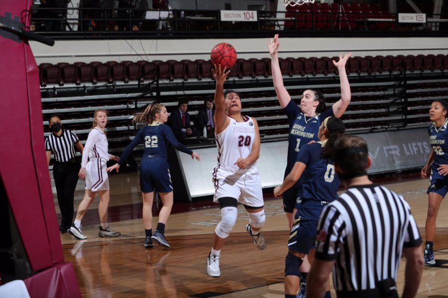 kendell heremaia makes a shot with two colonials players around her