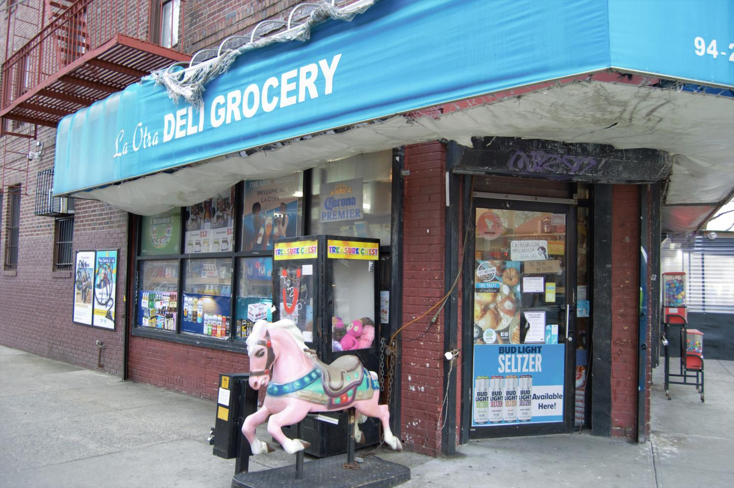a carousel horse in front of a jackson heights grocery store