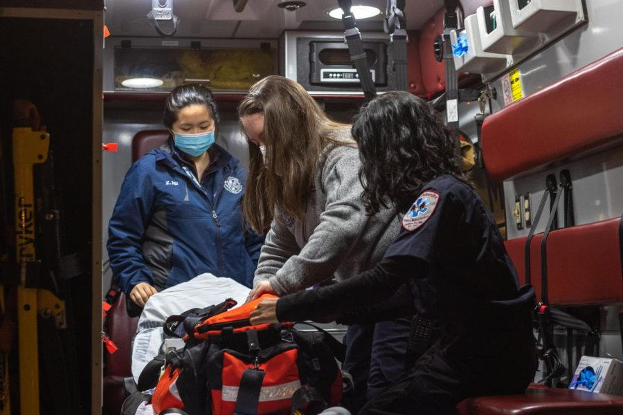 Three Fordham EMT students check a medical bag in an ambulance.