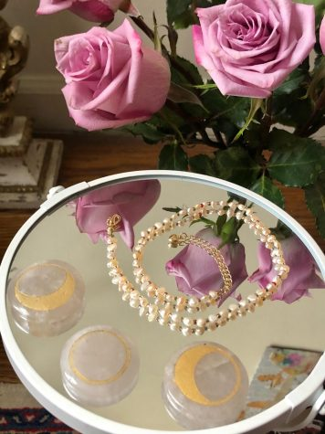 a solace jewelry necklace on top of a mirror with roses next to it