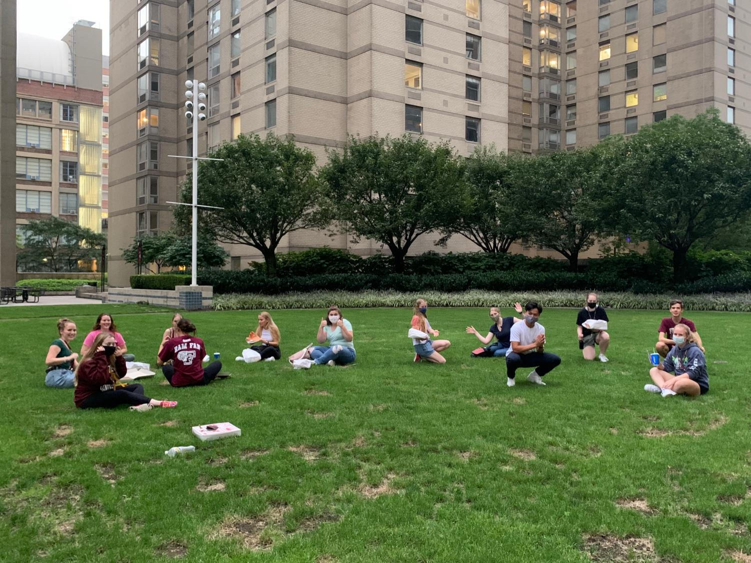 photo of first years sitting on the campus green
