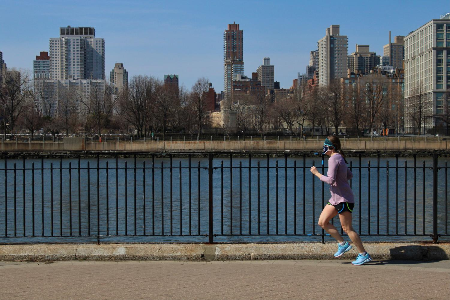 woman running in front of a body of water with a skyline in the background