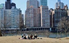 group of people having a spring picnic on the lawn of a park with a skyscraper in the background