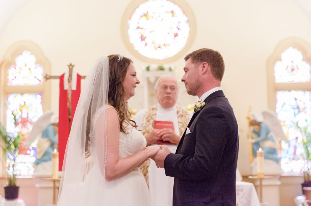 a bride and groom facing each other at the altar with denniston in the background officiating