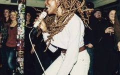 for an article on Kiki's Fashion Korner, Kia Warren singing into a microphone wearing a white suit