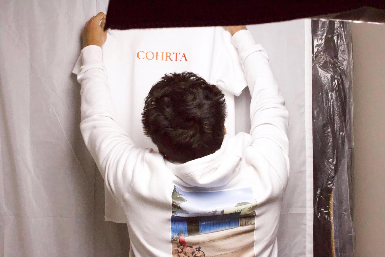 Someone holding up a COHRTA shirt