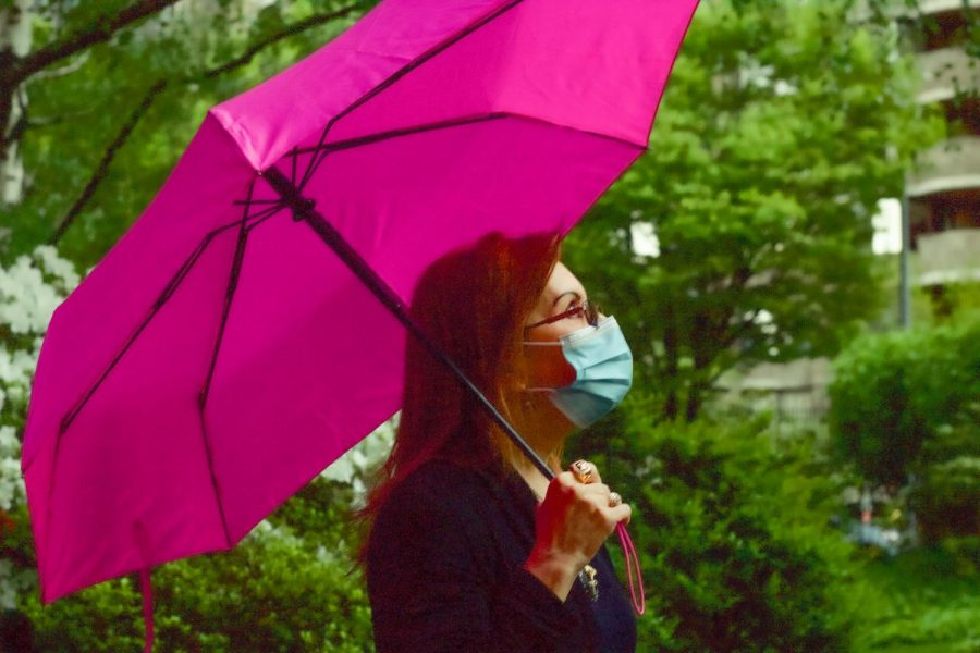 in an article about COVID-19, Angela LoCascio poses with a pink umbrella