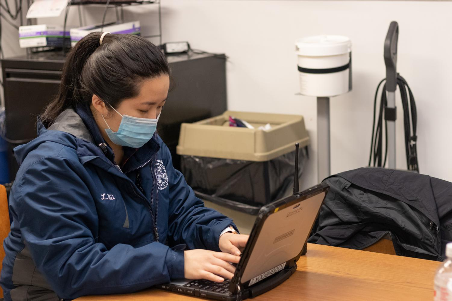 Li Ying Wei works on a laptop on her Fordham EMT job.