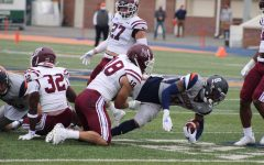 A Fordham football player tackles a Bucknell University player.