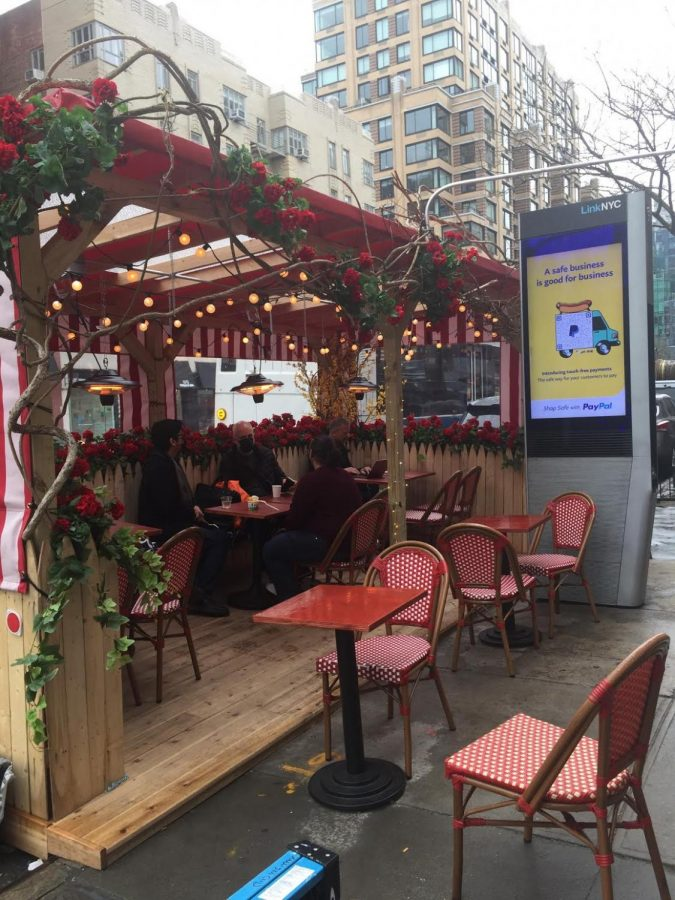 A photo of an outdoor dining booth at Pasta by Hudson. It is built out of wood and has five sets of tables and chairs inside. There is a group of people sitting at one of them. The sky is grey and bright, and the sidewalk is freshly wet from the rain.
