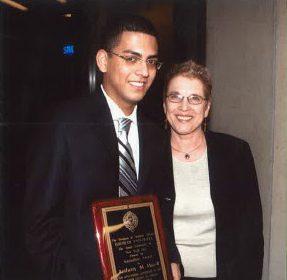 Image of Anthony Hazell and Dr. Elizabeth Stone, with Hazell holding an award.