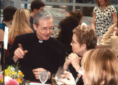 Elizabeth Stone and a catholic priest at an outdoor event in the Lincoln Center plaza.