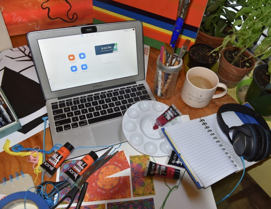 for an article about covid-19 photos, a student's computer with Zoom open and art supplies and notebooks