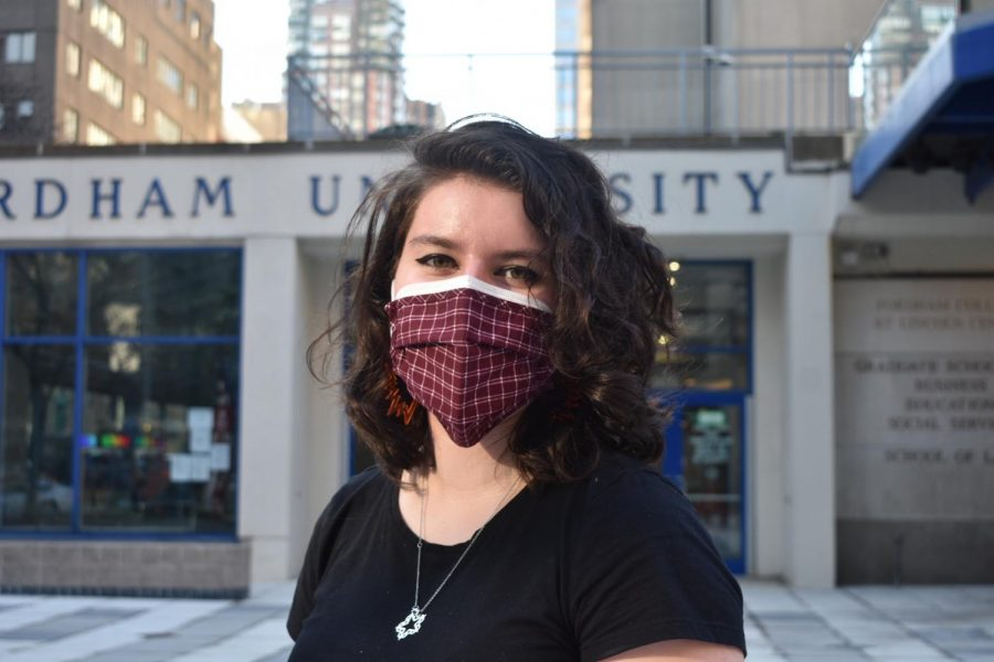 for an article about covid-19 photos, a student poses in two masks, one disposable underneath and one cloth outside, in front of Fordham Lincoln Center