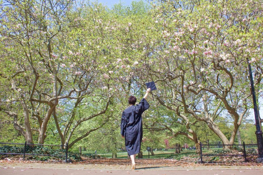 for an article about covid-19 photos, a student, facing away from the camera, carries their graduation cap wearing a gown in Central Park