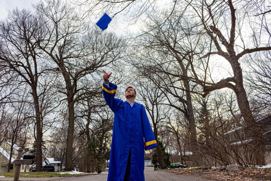 for an article about covid-19 photos, a graduating student tosses their cap in the air outside