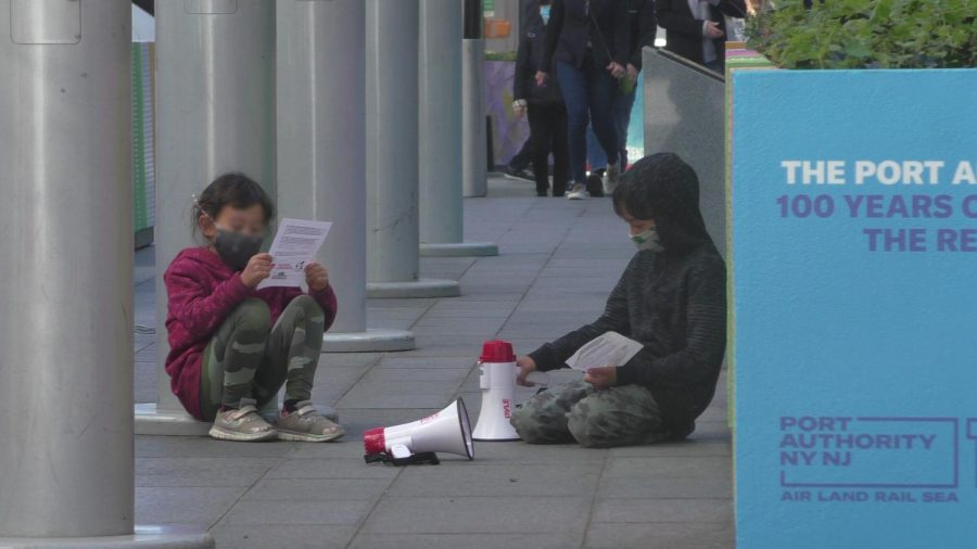 Two children reading pamphlets at a May Day rally.