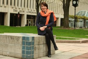 Laura Auricchio loves the newspaper and is the newest dean. she sits, smiling, on the plaza with an orange scarf and black dress