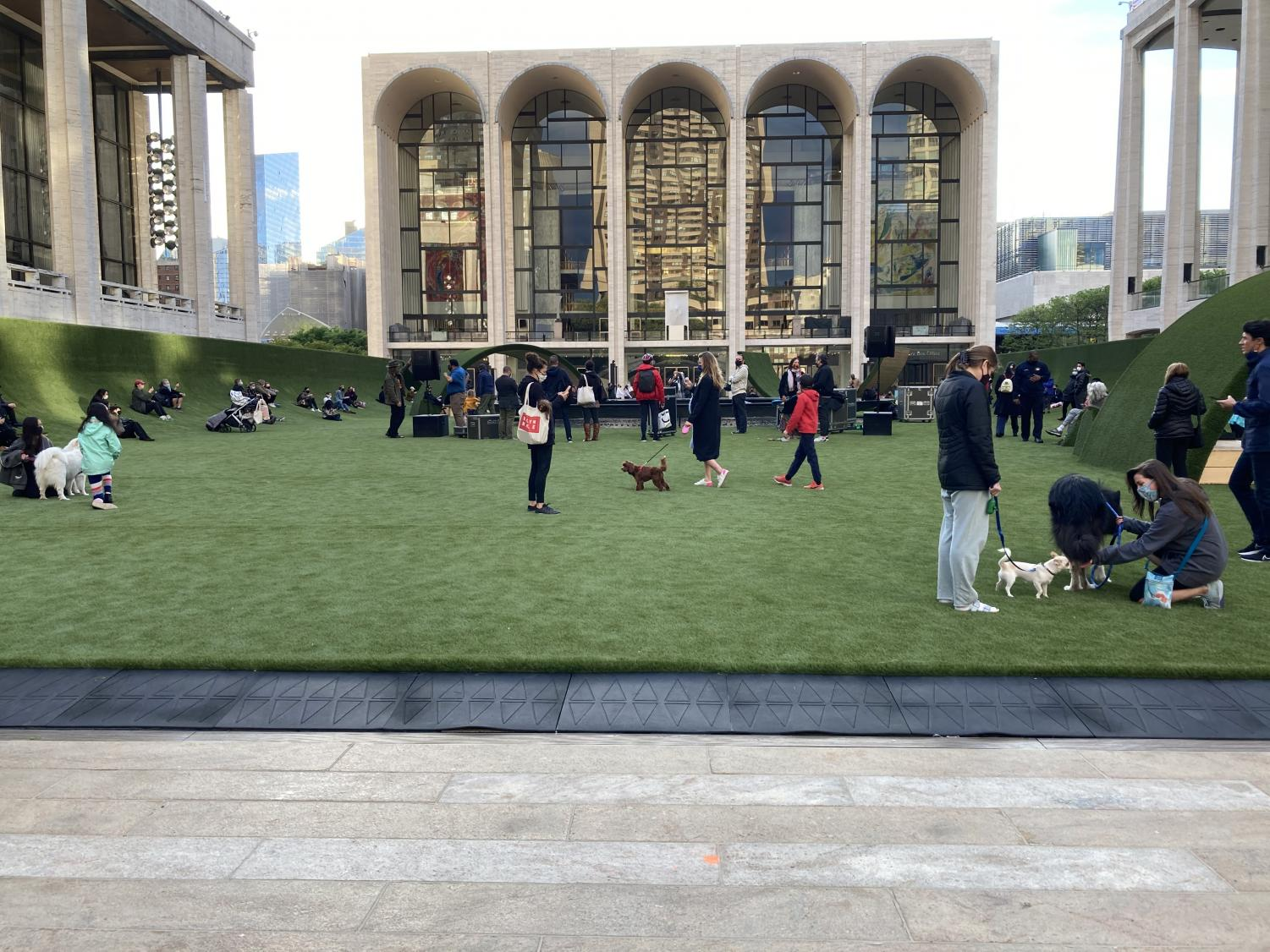 New Yorkers are walking along The GREEN at Lincoln Center with their dogs and children with the Metropolitan Opera House behind them.